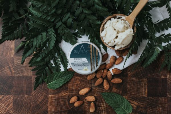 BluPeak Botanics 2000 mg CBD Cooling Salve with shea butter in spoon and almonds/plants spilled out onto wood table