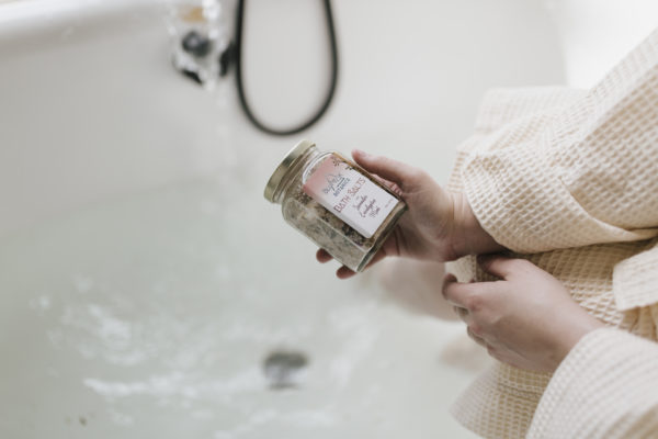 Womans hands holding BluPeak Botanics Bath Salts above the tub with water in it