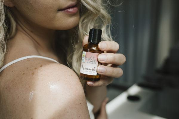 Woman holding BluPeak Botanics 500 mg CBD Nourish Body Oil over her shoulder