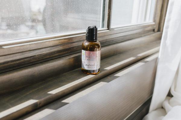 BluPeak Botanics 500 mg CBD Nourish Body Oil on a window sill