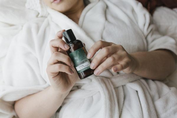 Woman holding BluPeak Botanics 500 mg CBD Massage Oil in her hand while wearing a robe