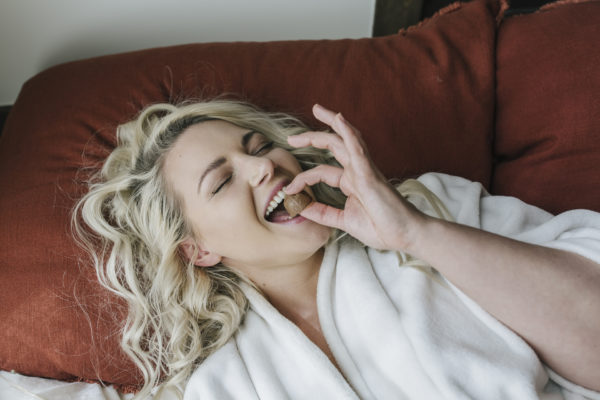 Woman lying on pillow eating BluPeak Botanics Indulgent Chocolate