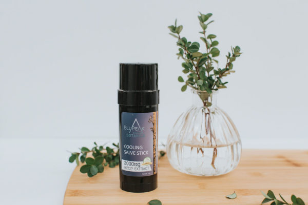 BluPeak Botanics 2000 mg CBD Cooling Salve on a board with a vase with water and plant in it