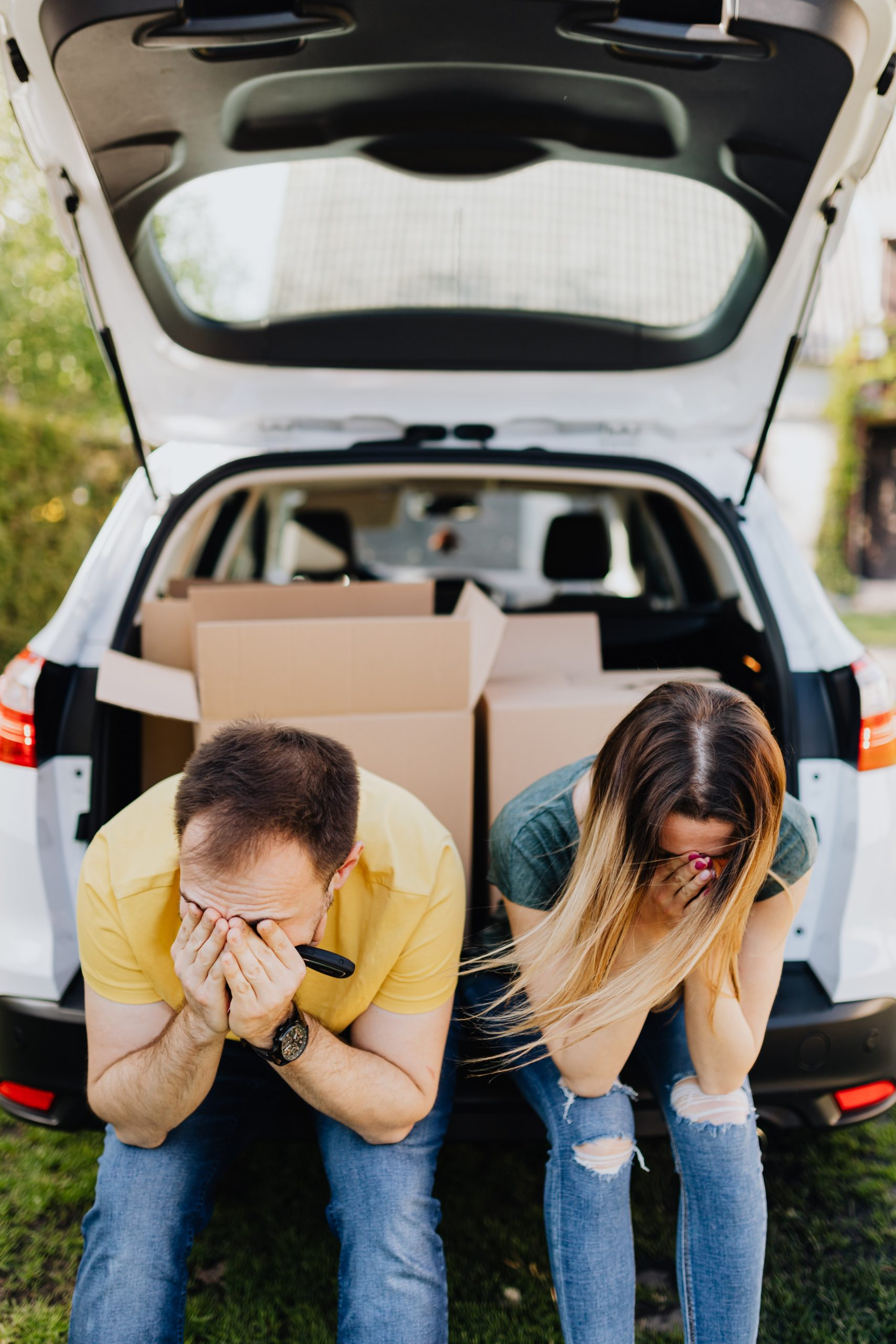 Stressed out Couple sitting in back of vehicle with moving boxes in it.